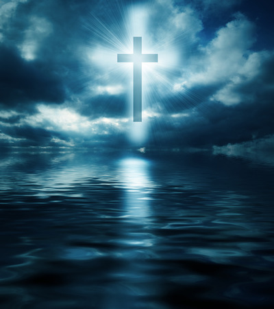 A cross floating above the waters at night. Stock Photo