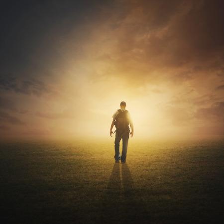 夕暮れ時はフィールドを介して歩く男。
