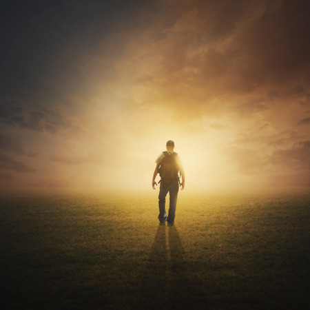 A man walking through the field at sunset.