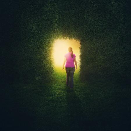 A woman walks through a door inside a grass wall.
