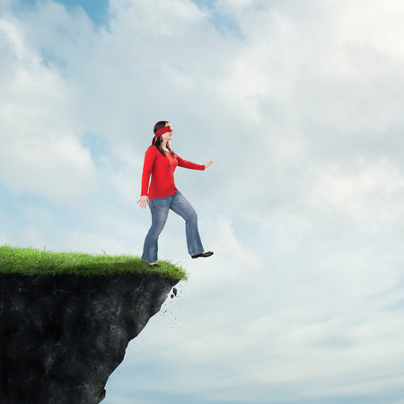 A woman walking off of a cliff while blindfolded.