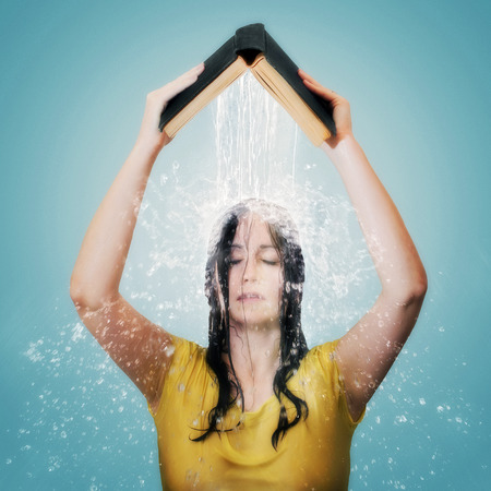Woman holding up a Bible with water pouring down on her head.