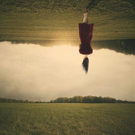 Surreal woman walks through a field upside down.