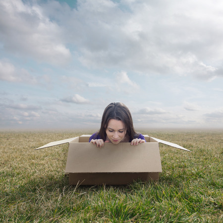 Surreal image of a woman stuck inside a small cardboard box.