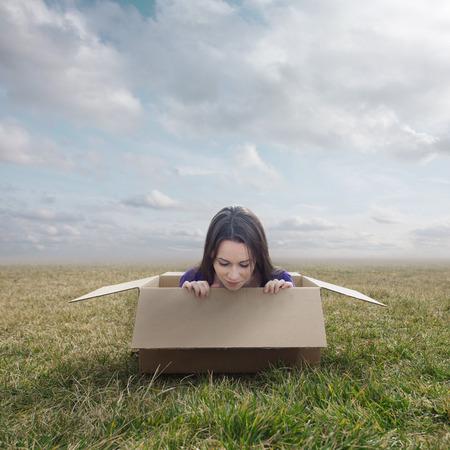 stuck: Surreal image of a woman stuck inside a small cardboard box.