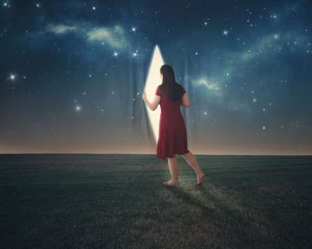 A woman pulls back the curtains and looks behind the night sky.