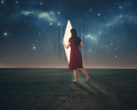 leuchtend: Eine Frau zieht die Vorhänge zurück und schaut hinter den Nachthimmel.