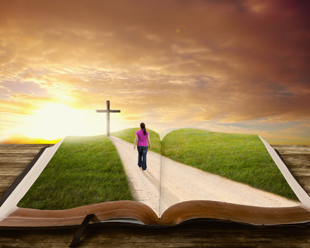 Een vrouw loopt langs een weg op een boek in de richting van het kruis. Stockfoto