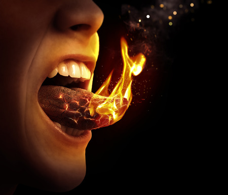 spicy: Close up of a tongue that is on fire.