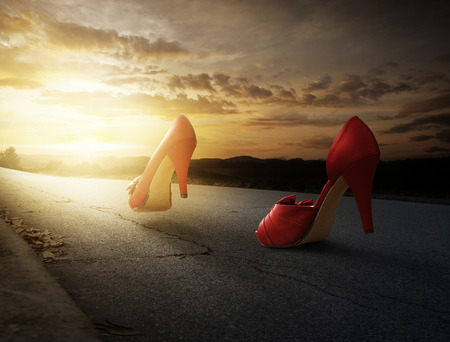 lonely road: A pair of high heels walking down a road at sunset.
