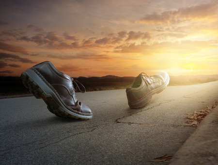 A pair of boots walk down the road at sunset