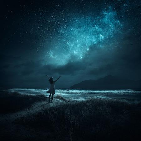 estrellas: Una mujer que levanta las manos en alabanza a altas horas de la noche.