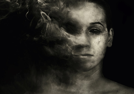 horrors: Womans face fading into smoke Stock Photo