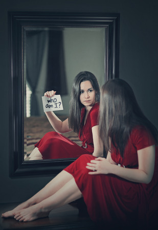 self: A woman looking into a mirror and asking who am I? Stock Photo