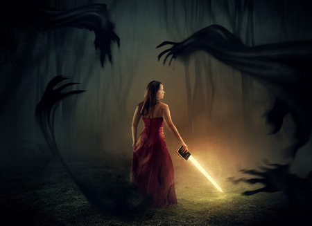 A woman holds a sword out of a Bible with dark demons around.