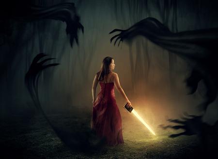 biblia: Una mujer sostiene una espada de una Biblia con los demonios oscuros alrededor.