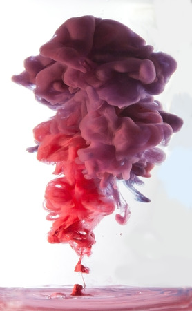 Red and purple ink dropped into water