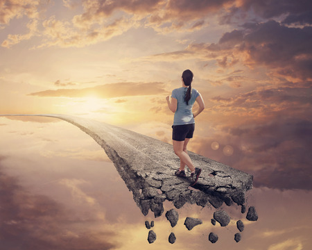 A woman runs along a road that is falling apart.