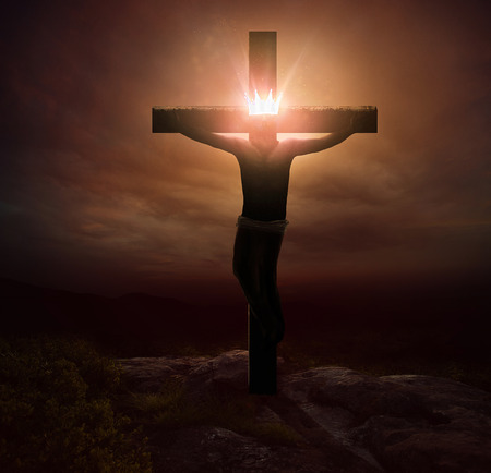 Jesus hanging on the cross with a glowing crown.
