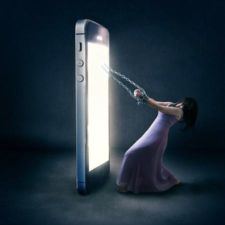 Een vrouw is gebonden door kettingen op haar mobiele telefoon.
