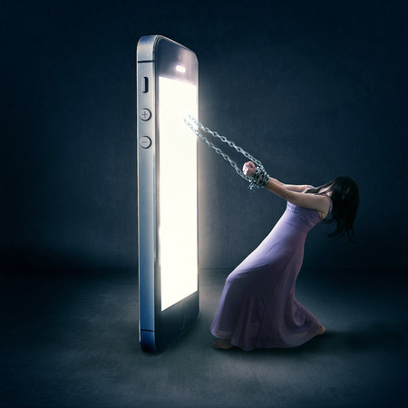 A woman is bound by chains to her cell phone.
