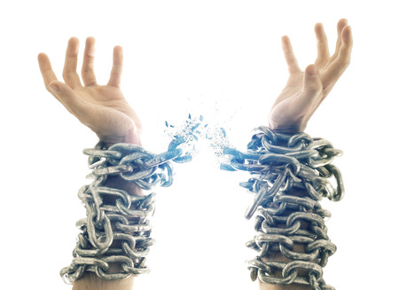 Two hands in chains that are breaking apart.