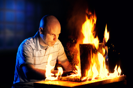 engulfed: A man uses a laptop while it is engulfed in flames.