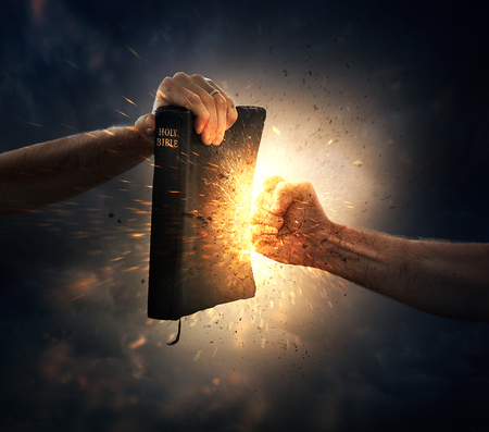 A fist punches into a Bible. Stock Photo
