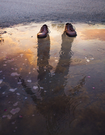 Two shoes standing in a puddle with reflection