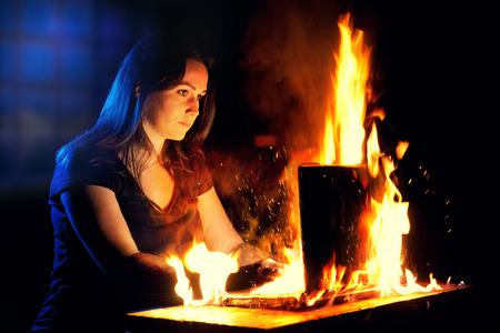 engulfed: A woman uses a laptop while it is engulfed in flames.