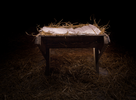 Empty manger in the straw at night.