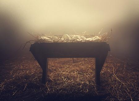 Eine leere Krippe in der Nacht unter dem Nebel.