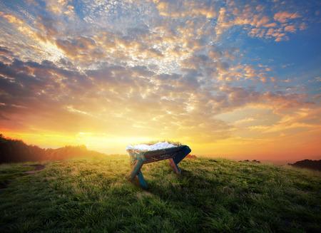 An empty manger in a grass field at sunset.