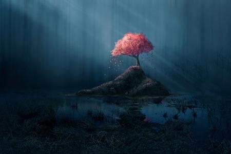 Un arbre rose seule dans une forêt bleu foncé. Banque d'images - 50560976