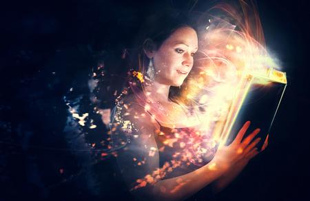 Una donna legge una Bibbia con brillanti luci incandescenti.