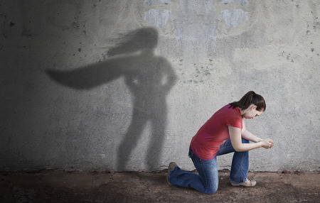 A woman prays while her shadow is a superhero.