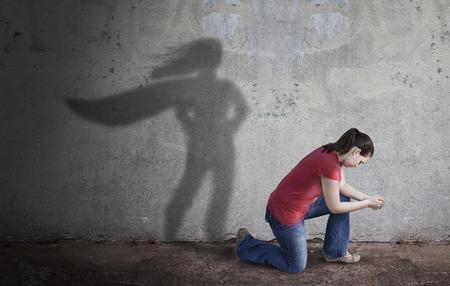 Kobieta modli się, a jej cień jest superbohaterem. Zdjęcie Seryjne