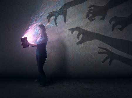 A woman holds a glowing Bible with scary hands in the background. Banque d'images