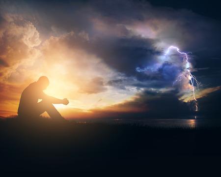 tormenta: Un hombre está rezando a través de la salida del sol y la tormenta Foto de archivo