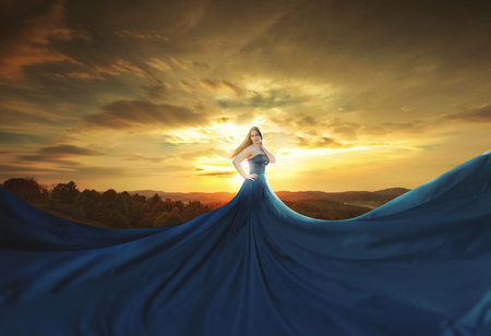 surreal: A woman wearing a huge blue dress at sunset