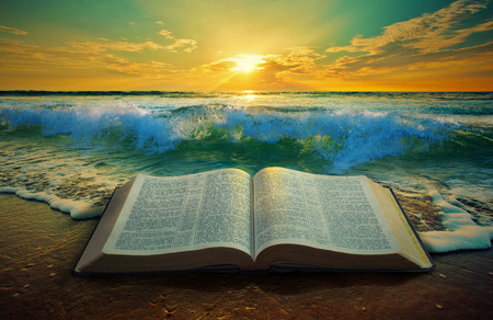 Close up of ocean waves at sunrise with a Bible