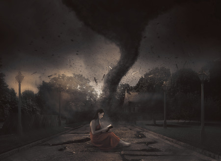 A woman reads her Bible in the midst of a tornado 스톡 콘텐츠