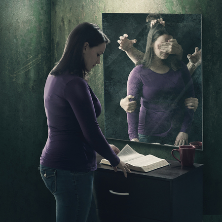 A woman reads her Bible as demons try to stop her Foto de archivo