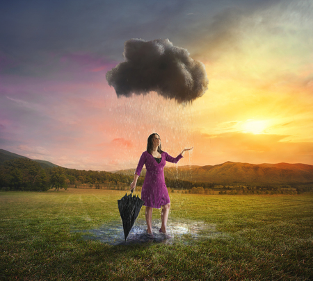 A woman gets soaked by a single dark cloud.