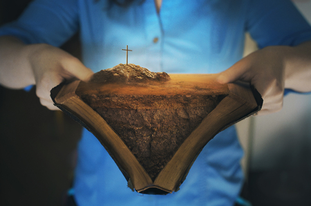 An open Bible with the landscape of the story of the cross.