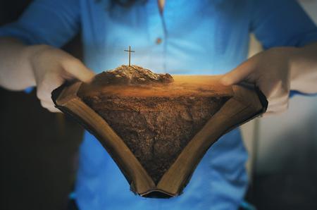 Een open Bijbel met het landschap van het verhaal van het kruis.