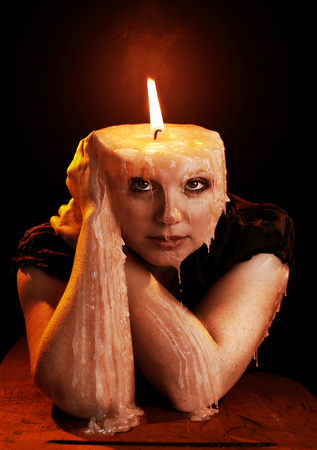 A woman in the shape of a candle is melting away. Stock Photo