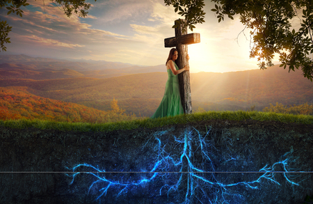 A woman clings to a wooden cross, with glowing roots. Stockfoto
