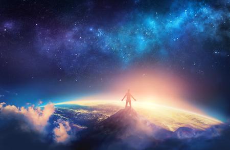 Een man beklimt een hoge berg en legt zijn armen omhoog in lof