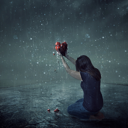 A woman offers up her broken heart during a rain storm Фото со стока - 81659698